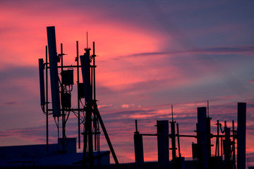 Silhouette of cellular tower with beautiful sunset cloudy sky