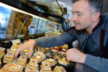 Baker collecting cake from counter