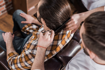 high angle view of barber combing hair of customer at barbershop