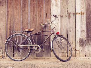 cyclists outdoor lifestyle. Classic vintage retro bicycle against the wooden old crack wall at home in Asia countryside. Old bike vintage style background