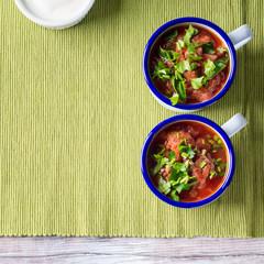 Russian beetroot soup borscht in enamel mugs on green cloth