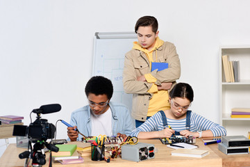 teen boy watching how multicultural friends soldering computer circuit with soldering iron at home