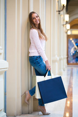 Young happy woman with some shopping bags in the mall