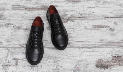 Black leather sneakers on a light laminate.