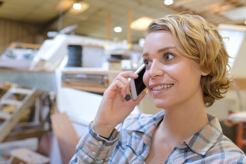 woman using phone in a warehouse