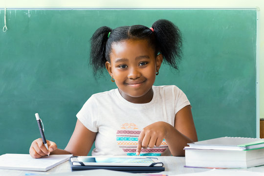 Little african student sitting at desk with blank black board in background.
