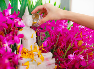 Sprinkle water onto a Buddha image, a gesture of worship during the annual Songkran festival.