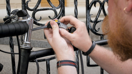 Closeup image of young man locking bicucle with combination lock