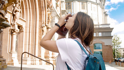 Portrait of young brunette tourist girl making photos on vintage film camera