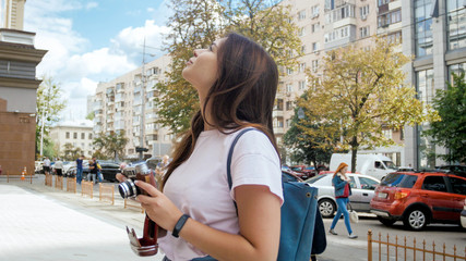 Beautiful brunette girl with vintage film camera and bag standing on street