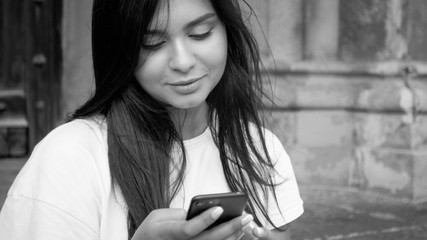 Black and white photo of beautiful brunette woman with long hair browsing internet on mobile phone