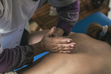 Therapist doing oriental massage with hands to woman.