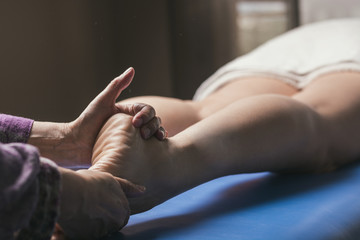 Therapist doing foot reflexology massage on patient.