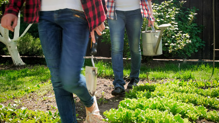 Closeup photo of family walking at backyard garden with gardening tools