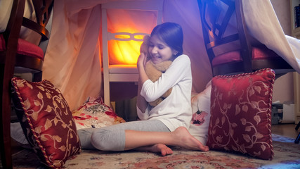 Cute girl playing with teddy bear in bedroom at night
