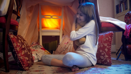 Cute little girl with teddy bear in tepee tent at nioght