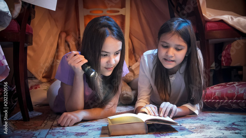 Closeup portrait of two teenage girls with flashlight lying on floor closeup portrait of two teenage girls with flashlight lying on floor and reading scary book sciox Gallery