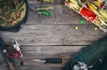 Fishing tackle - fishing spinning, hunting knife, hooks and lures, a fishing net and overalls. On a wooden background, top view. Copy space