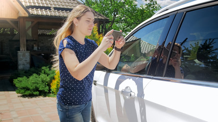 Portrait of young woman taking photos of car for insurance company