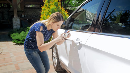 Young woman making photographs of her car on mobile phone