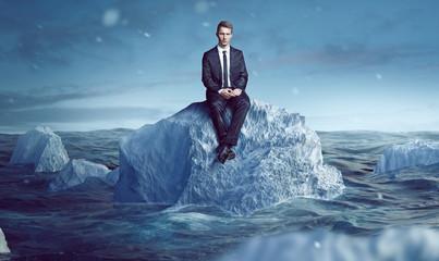 Geschäftsmann sitzt auf Eisberg im Meer