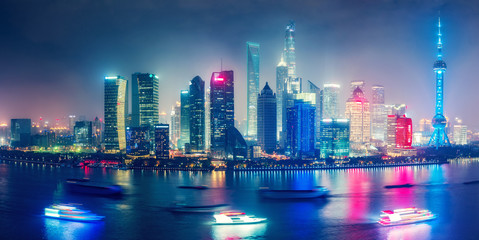 Aerial panoramic view over a big modern city by night. City illuminations of Shanghai, China. Colourful skyline with skyscrapers and river Huanpu.