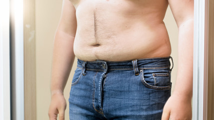 Closeup photo of big fat hairy belly of young shirtless man