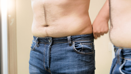 Closeup photo of young man with big hairy belly