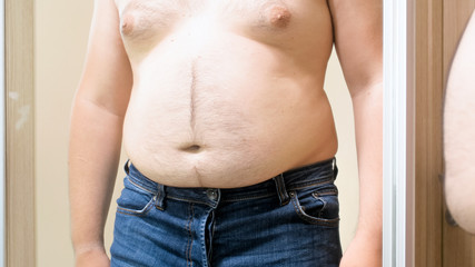 Shirtless man in jeans with big fat belly