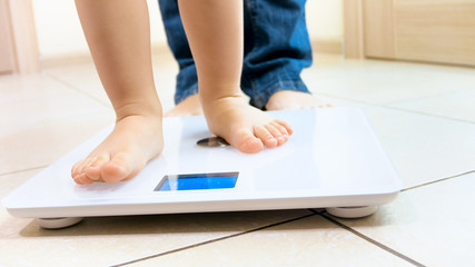 Closeup image of baby's feet standing on digital weight scales