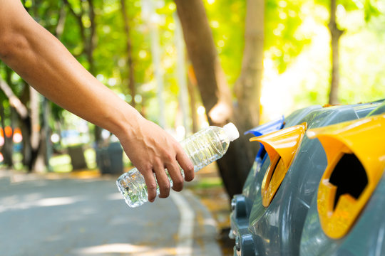 Closeup man hand throwing empty plastic water bottle into to recycling bin, environmental protection concept.