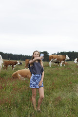 Teenage girl taking picture on pasture