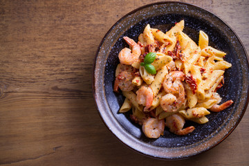 Shrimp penne with sun dried tomatoes and basil in creamy mozzarella sauce. Pasta with shrimps in bowl on wooden table. overhead, horizontal
