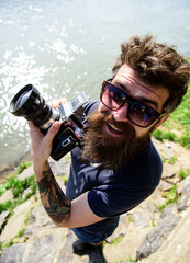Reporter photographer concept. Man with beard and mustache wears sunglasses, water surface on background. Hipster on smiling face holds old fashioned camera. Guy shooting nature near river or pond.