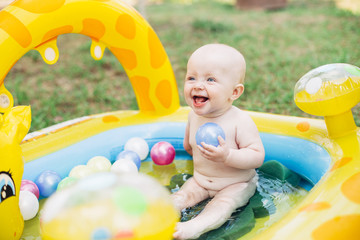Little baby girl playing in the swimming pool. Summer. Smiling.