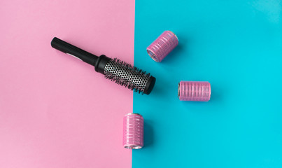 Black hairbrush and pink curlers on a pink blue background. Hairstyling concept.