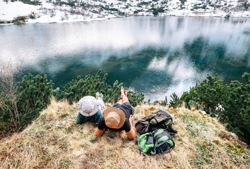 Father and son backpackers relax after long walk near the beautiful lake