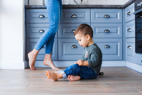 A cute little boy is sitting on the kitchen floor with his mother in the background