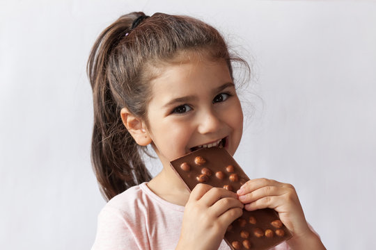 Cute child girl eating chocolate. Pretty child with chocolate.