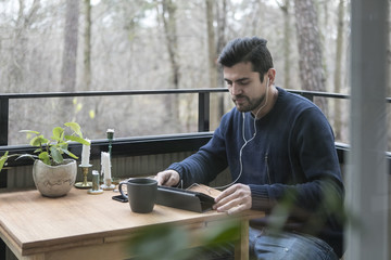 Man with headphones using digital tablet while sitting at table in balcony