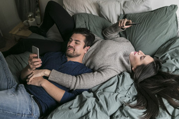 High angle view of couple using mobile phone while relaxing on bed at home