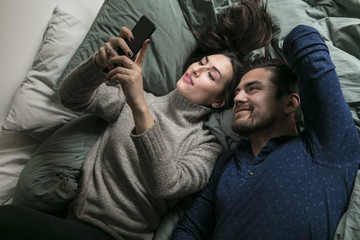 High angle view of smiling couple taking selfie through smart phone while lying on bed