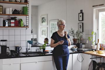 Senior woman talking on phone through headphones