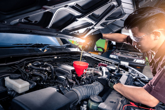 the wide angle image of the technician filling a new lubricant in the car's engine. the concept of automotive, repairing, mechanical, vehicle and technology.