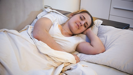 Portrait of young brunette woman sleeping in bed