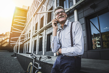 Sharing good business news. Handsome mature businessman talking on the mobile phon. Street landscape on background.