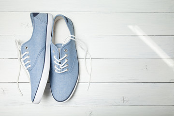 Summer casual sneakers on a white wooden background. Copy space for text.