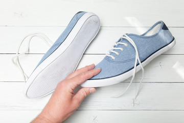 Man hand selects blue jeans sneakers on a white wooden background.