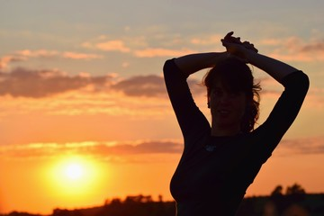 Young woman in sunset light, success, happiness, fitness concept