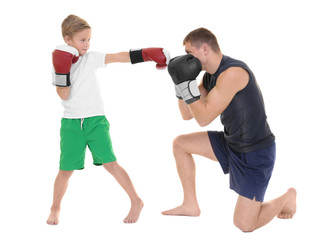 Cute little boy training with boxing coach on white background
